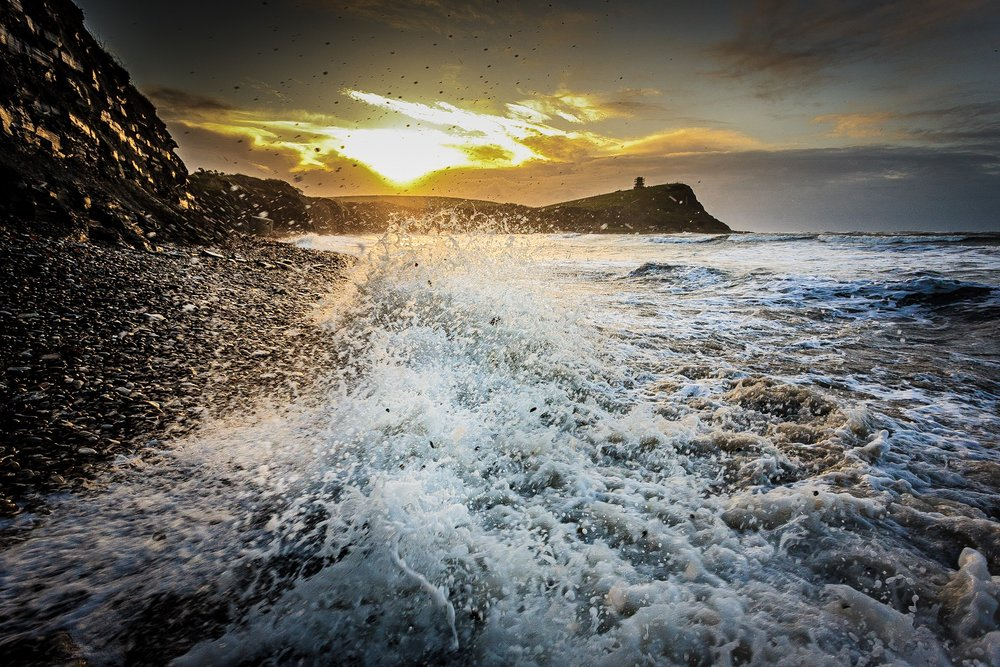 The picture of Kimmeridge Bay at sunrise with the crashing wave