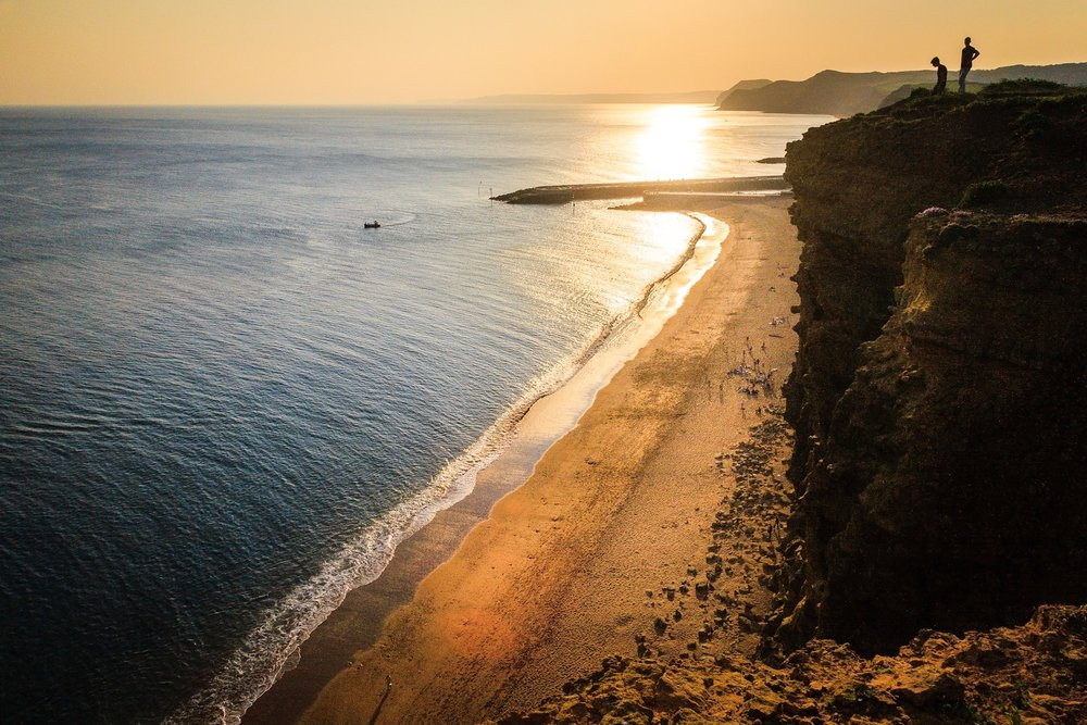 The view looking towards the sunset of the beach at West Bay. From the cliffs above