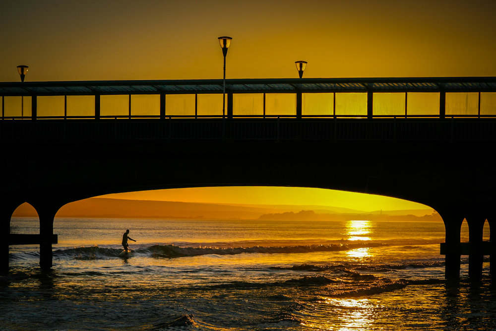 Surfer under the pier by Bournemouth Photographer Rick McEvoy