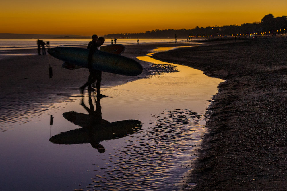 Surfers walking on the beach at sunset by Rick McEvoy Bournemouth Photographer