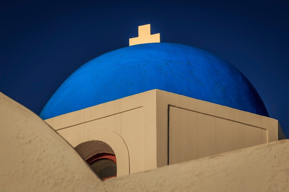 Picture of a blue domed church roof with cross illuminated by the sun. Santorini. Greece.