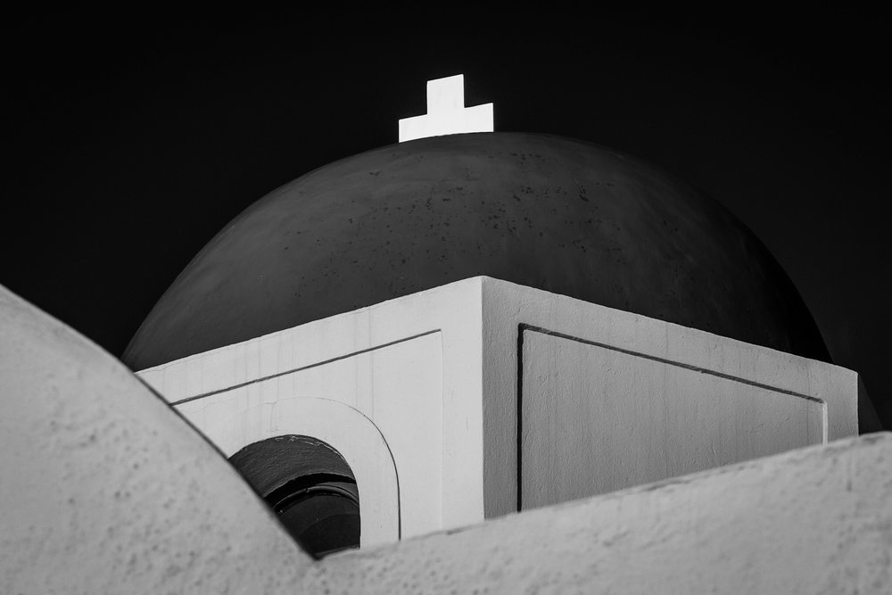 Black and white picture of a blue domed church roof in Santorini