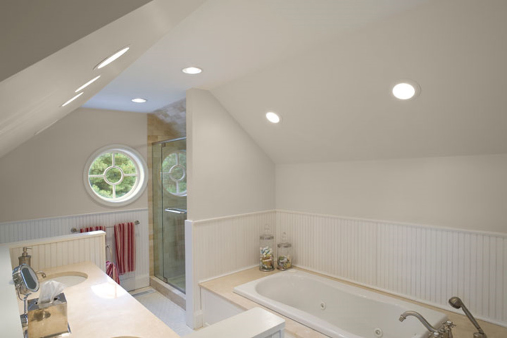 Because this master bath was created in a former awkward attic space, in order to appear architecturally appropriate to the exterior, we installed a round window in peak of the roofline. Beautiful on the inside…