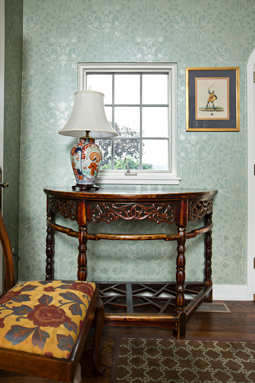 Mixing continents and centuries is the purview of a professional. Here, Brian Gibson chose an antique Northern Chinese demilune console table w European influence to add worldly detail to this window.
