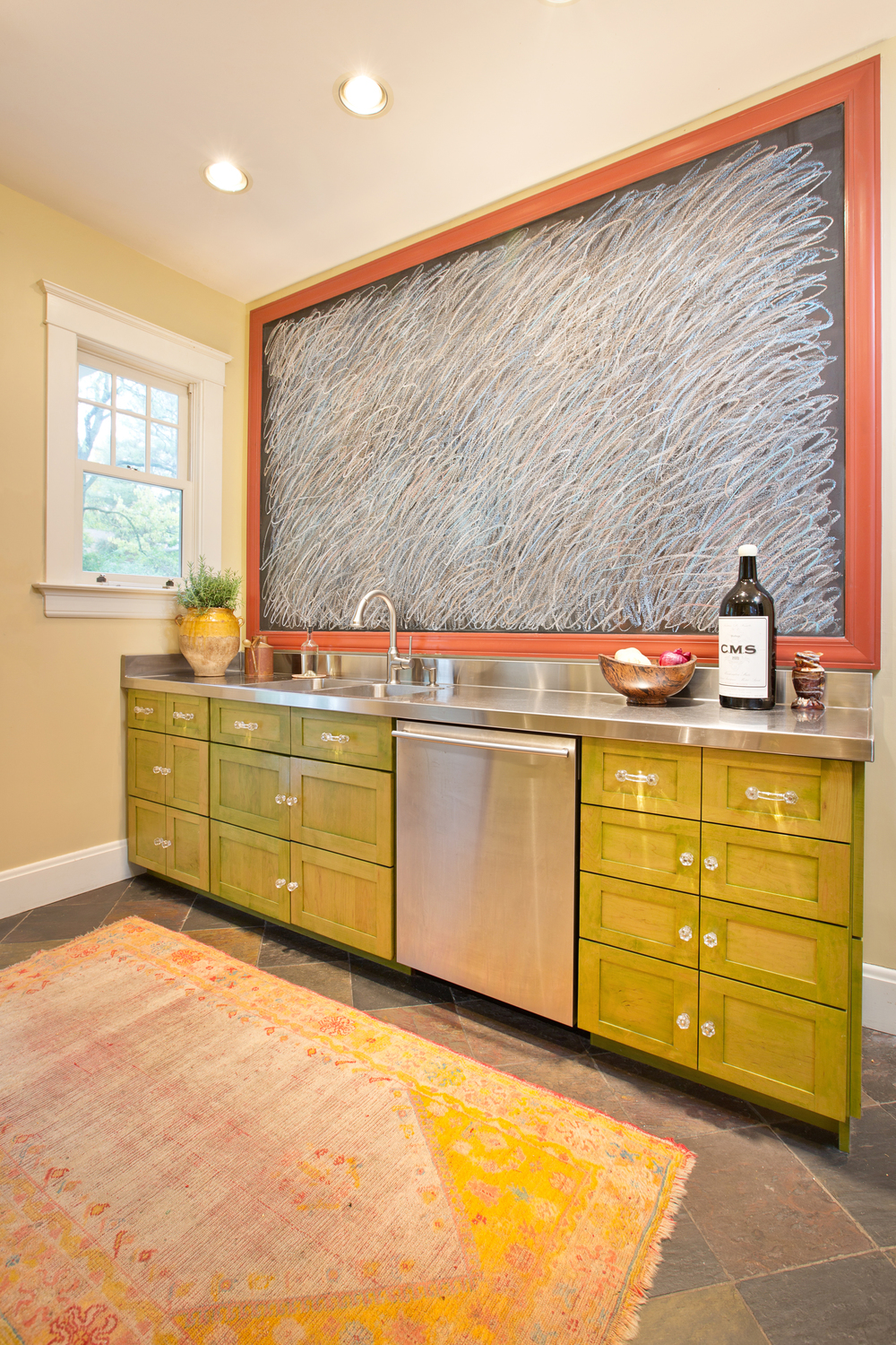This could have been an unremarkable galley kitchen. Not only did we make it uber-functional (little is the new big) but we added spice by staining the cabinets in a chartreuse wash and installing12x5 chalkboard (yes, that's a chalkboard) which this homeowner uses to channel her inner Cy Twombley