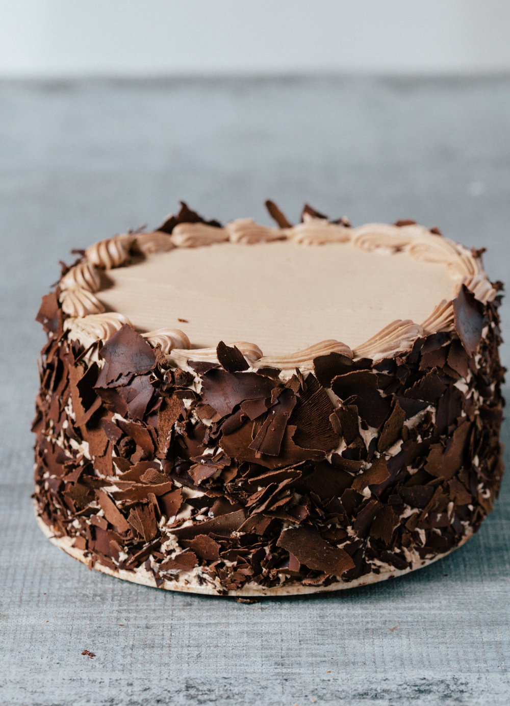 "Sacher Cake: This cake is three layers of velvety chocolate buttercream, spread over a moist Viennese chocolate sponge cake. The sides are covered in chocolate shavings. Available daily in 7"" round."