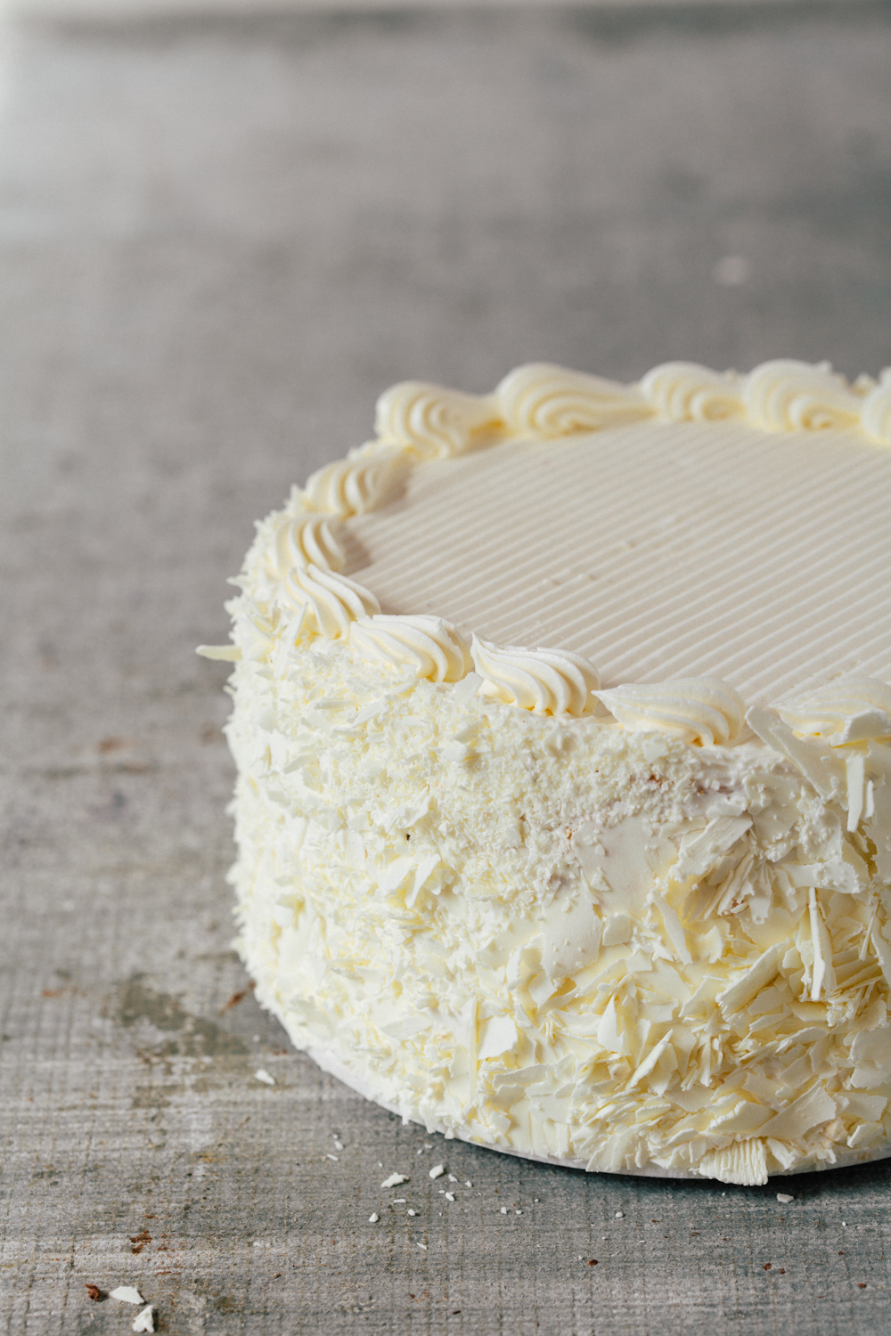 "Vanilla Cake: This cake is a three layer sponge cake and is filled with vanilla buttercream. White chocolate shavings cover the sides. Available daily in 7"" round."