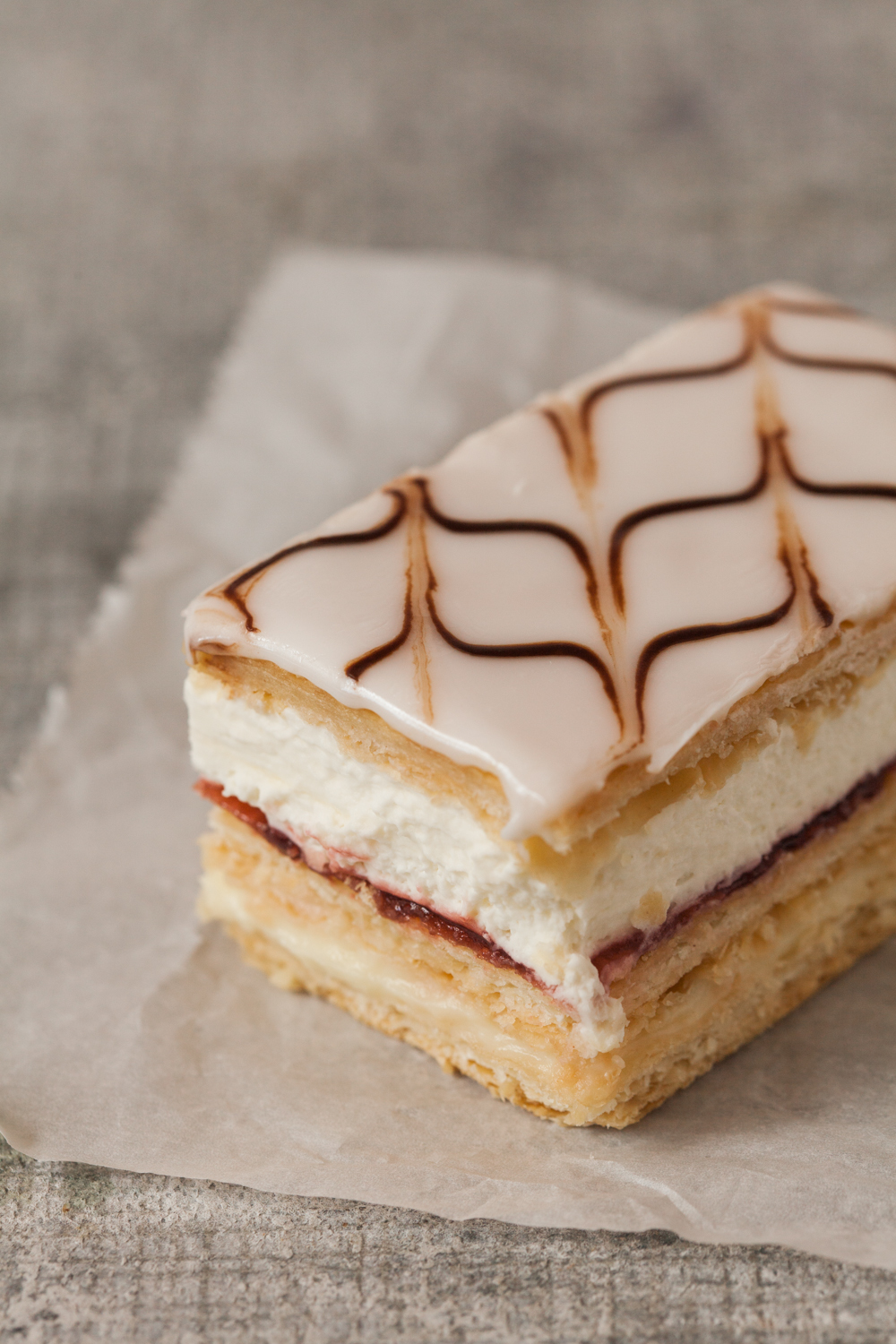 Napoleon:   The Napoleon has three layers of flaky French pastry, layered with vanilla custard, fresh whipped cream, and a hint of raspberry.  All of this deliciousness is enrobed in fondant. This pastry is as bold as the Emperor of France himself (though it wouldn't dare attempt a land-war in Asia).