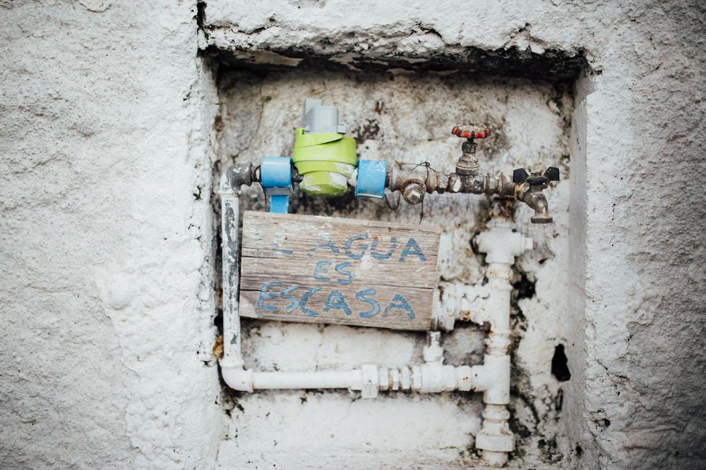 """El cabrero tuvo que poner el cartel porque la gente solía dejar el grifo abierto. // """"Water is scarce"""": The goat-herder had to write that in order to avoid people leaving the tap on"""