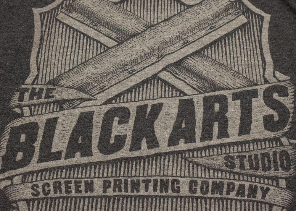 This is a clear discharge print on a Canvas brand Charcoal-Black Triblend t-shirt.  Triblend fabric is 50% polyester, 25% cotton, and 25% rayon.  As you can see the discharge ink only removes the color from the cotton which leaves a speckled vintage looking print.