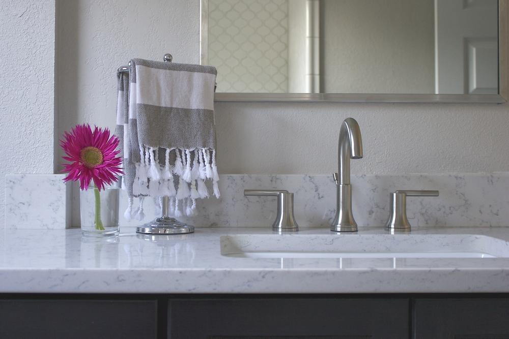 Sleek faucets match the sconces and mirror for a clean, modern look. The marble-like countertop, gray stained Shaker style cabinets, and soft shape of the Ogee wall tile lend the space its charm.