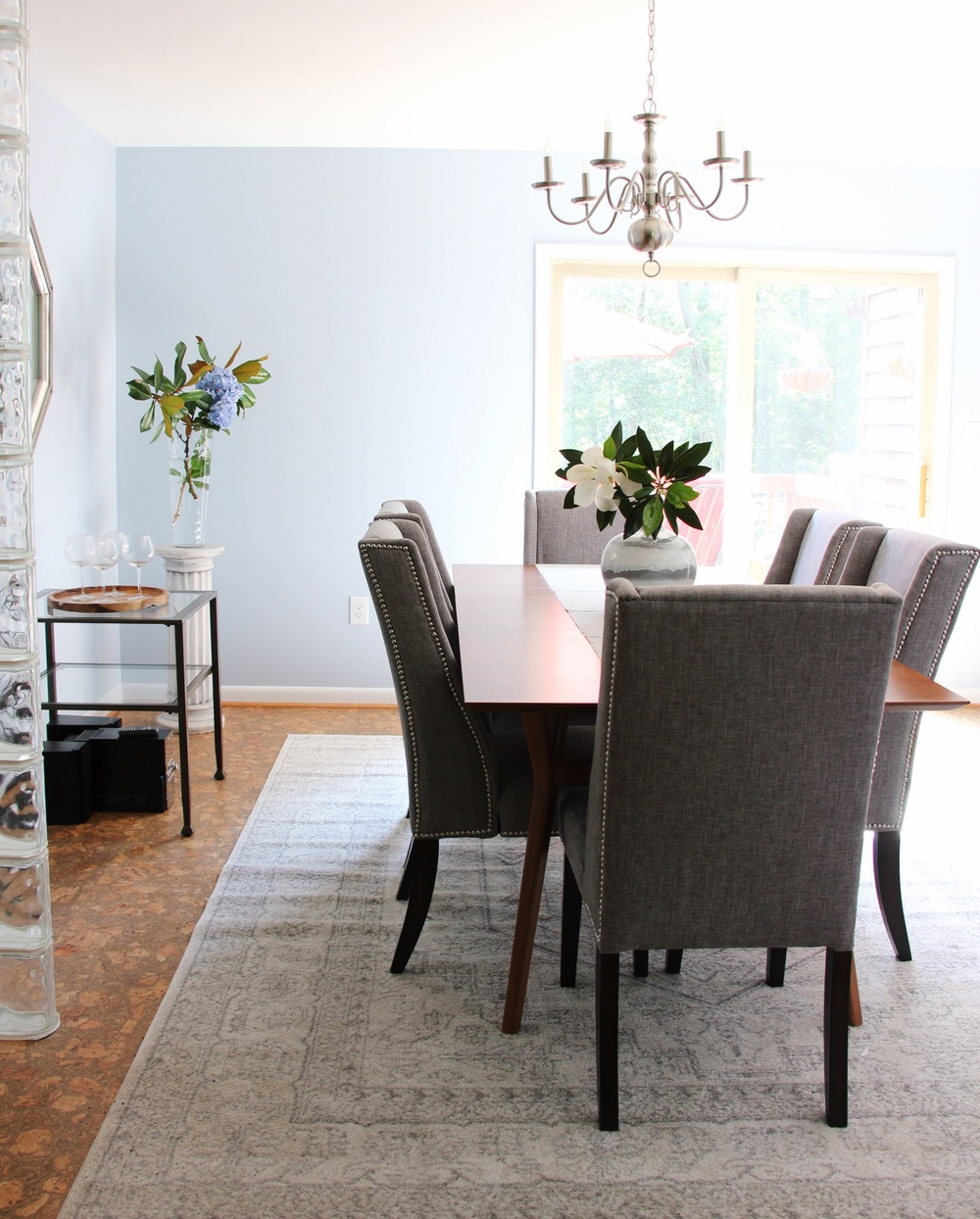 A classic rug in grays defines the dining room area and dresses up the space.
