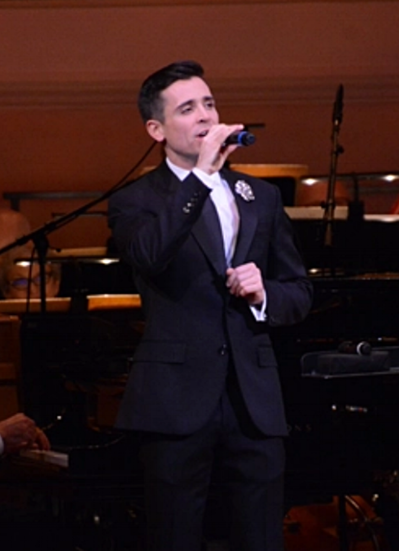 Matt Doyle, wearing Fleur'd Pins, singing on stage at Carnegie Hall.png