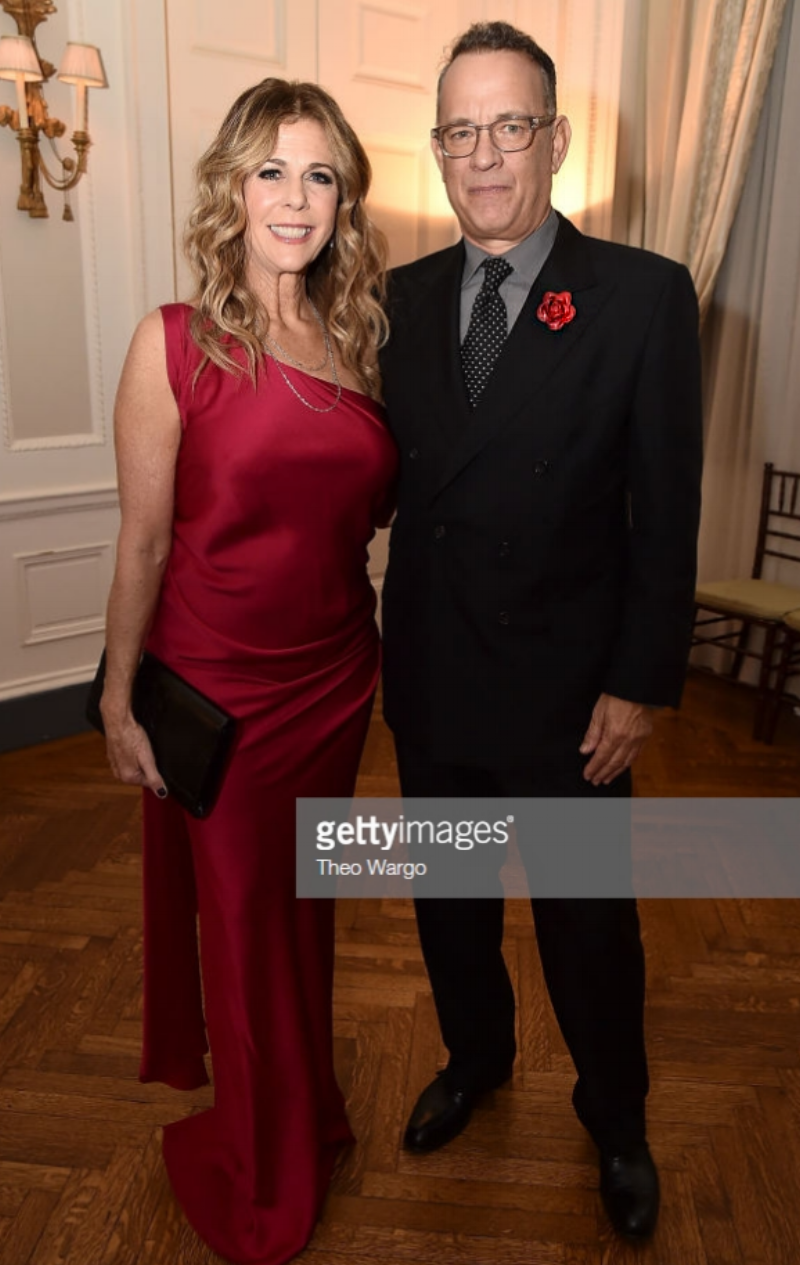 Tom Hanks, wearing Fleur'd Pins Red Leather Ella Rose, and Rita Wilson attend the American Friends of Blérancourt 2018 Annual Gala Dinner 11.10.18 at Colony Club in New York City. (Photo by Theo Wargo:Getty Images)   .png