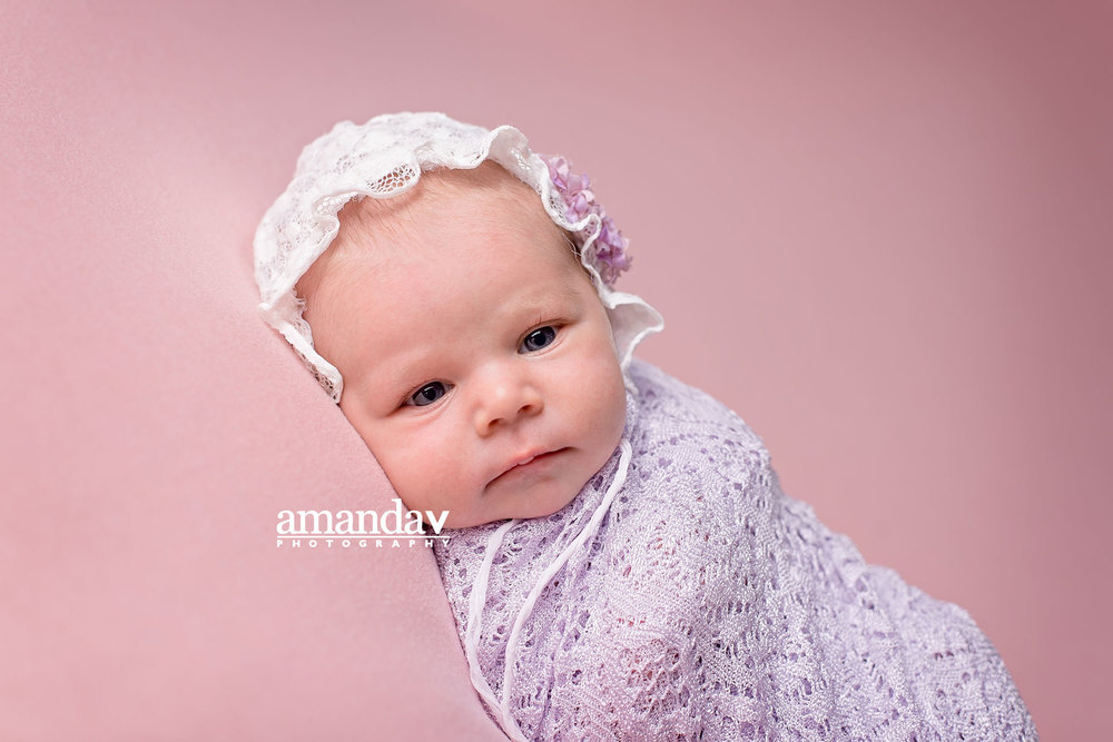 baby with bonnet swaddled in purple wrap