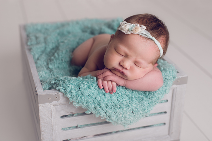 Baby in a crate in studio newborn session