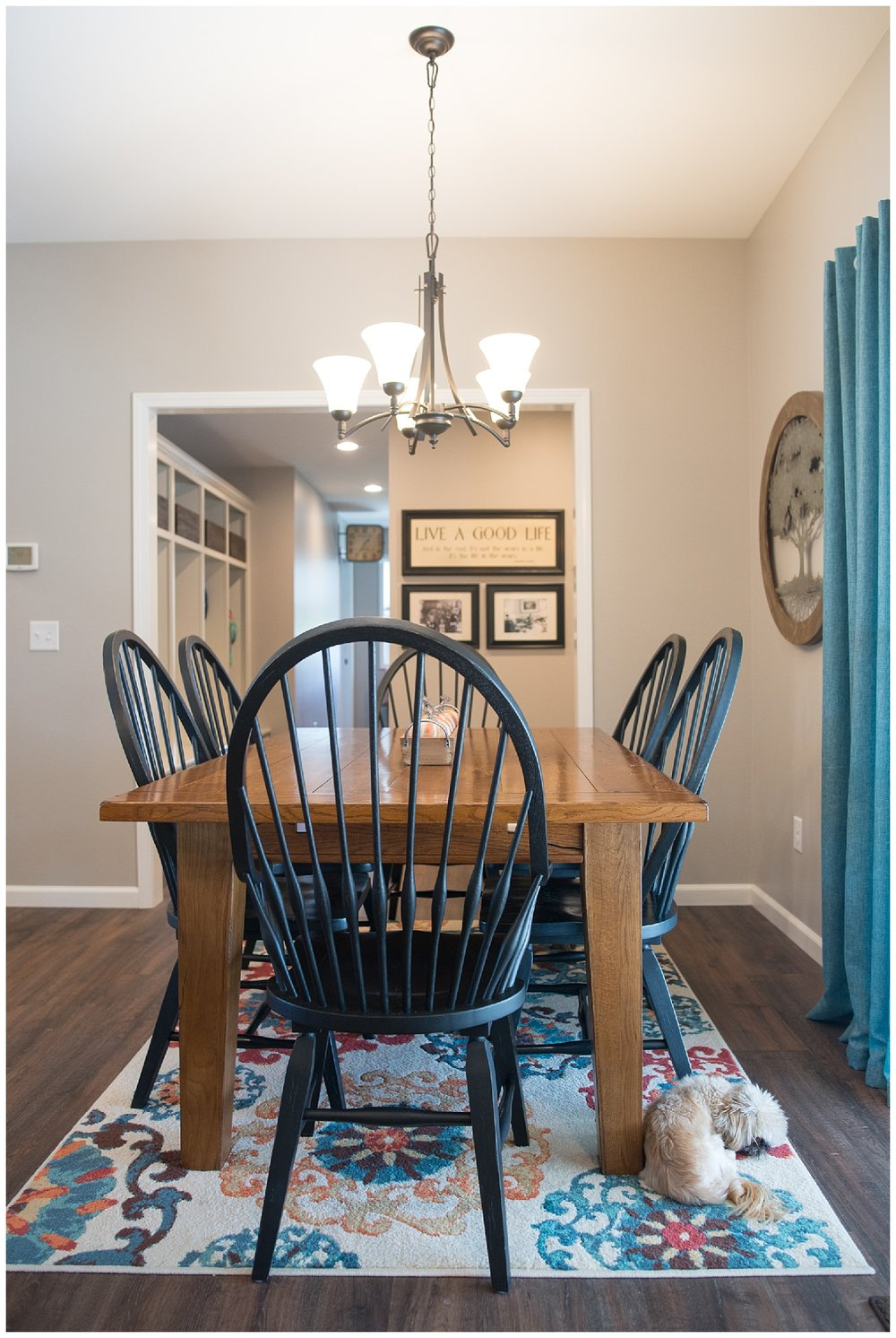The dining room table came from Uebinger's Furniture. There's little Gus lying on a gorgeous rug and looking out the patio door. She's hung black and white family photos under the Live A Good Life picture.