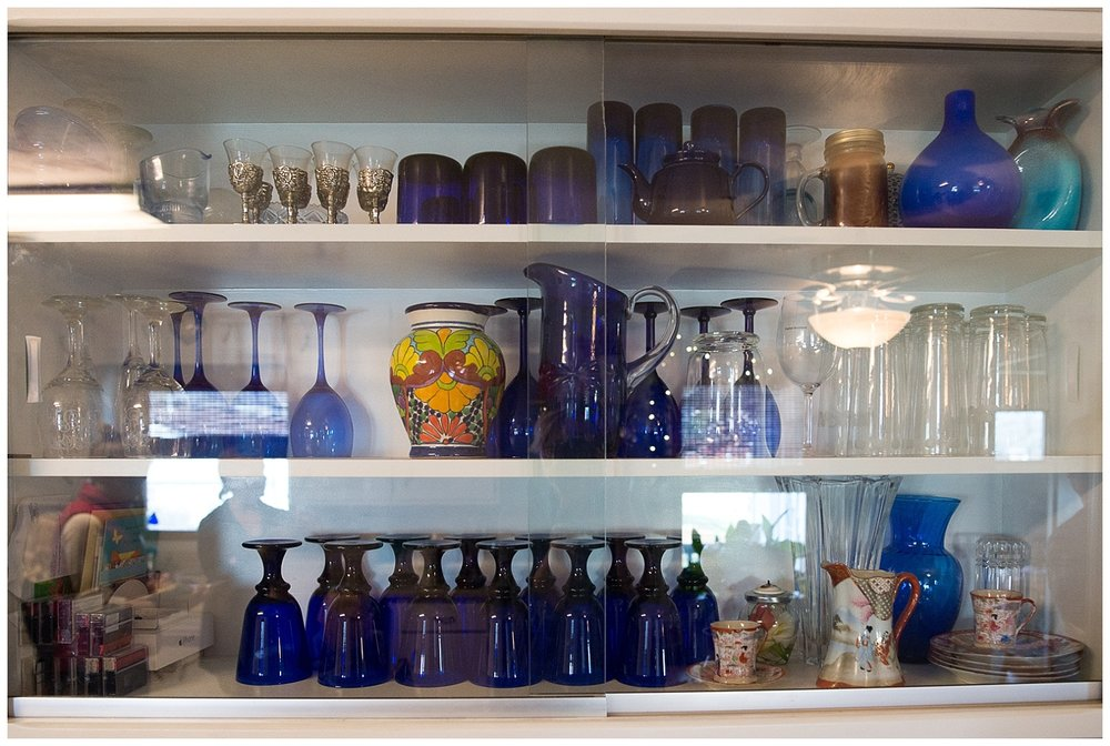 Monica fell in love with blue glass and has been collecting it since college.  The etched champagne flutes from her and Aaron's wedding as well as auction finds of her mother, Rita, reside in this cupboard. The glass allows her to display these lovely mementos of her life.