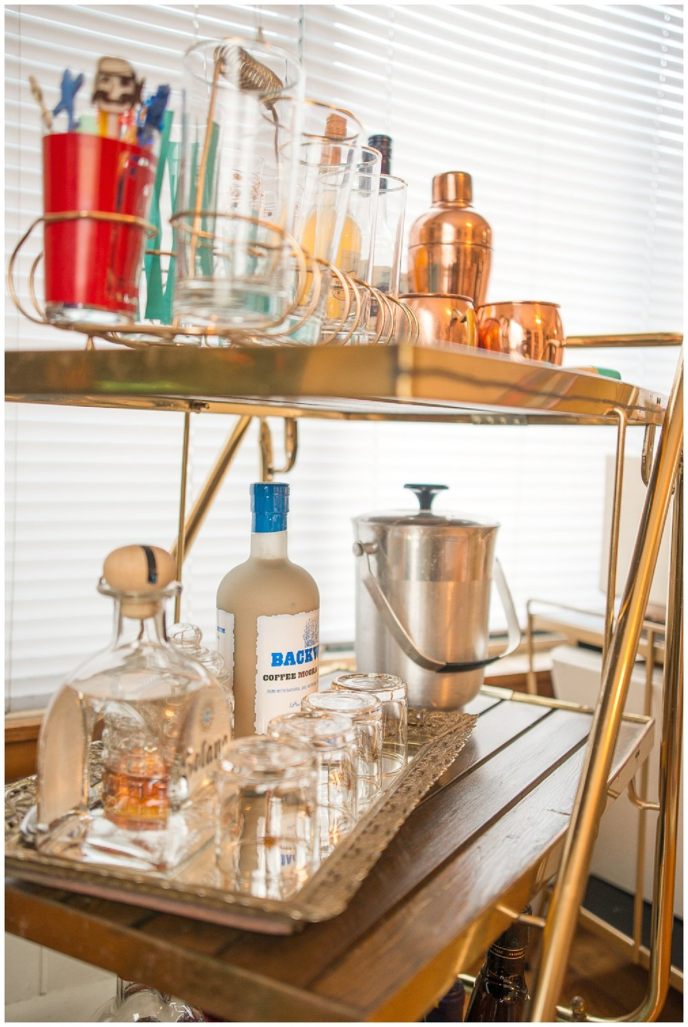 Her fave thing is this vintage bar cart that she got from Fresh Digs. Most of what's on it are thrift store finds. I love the gold glass carrier and the gold vanity tray she's using to hold barware.
