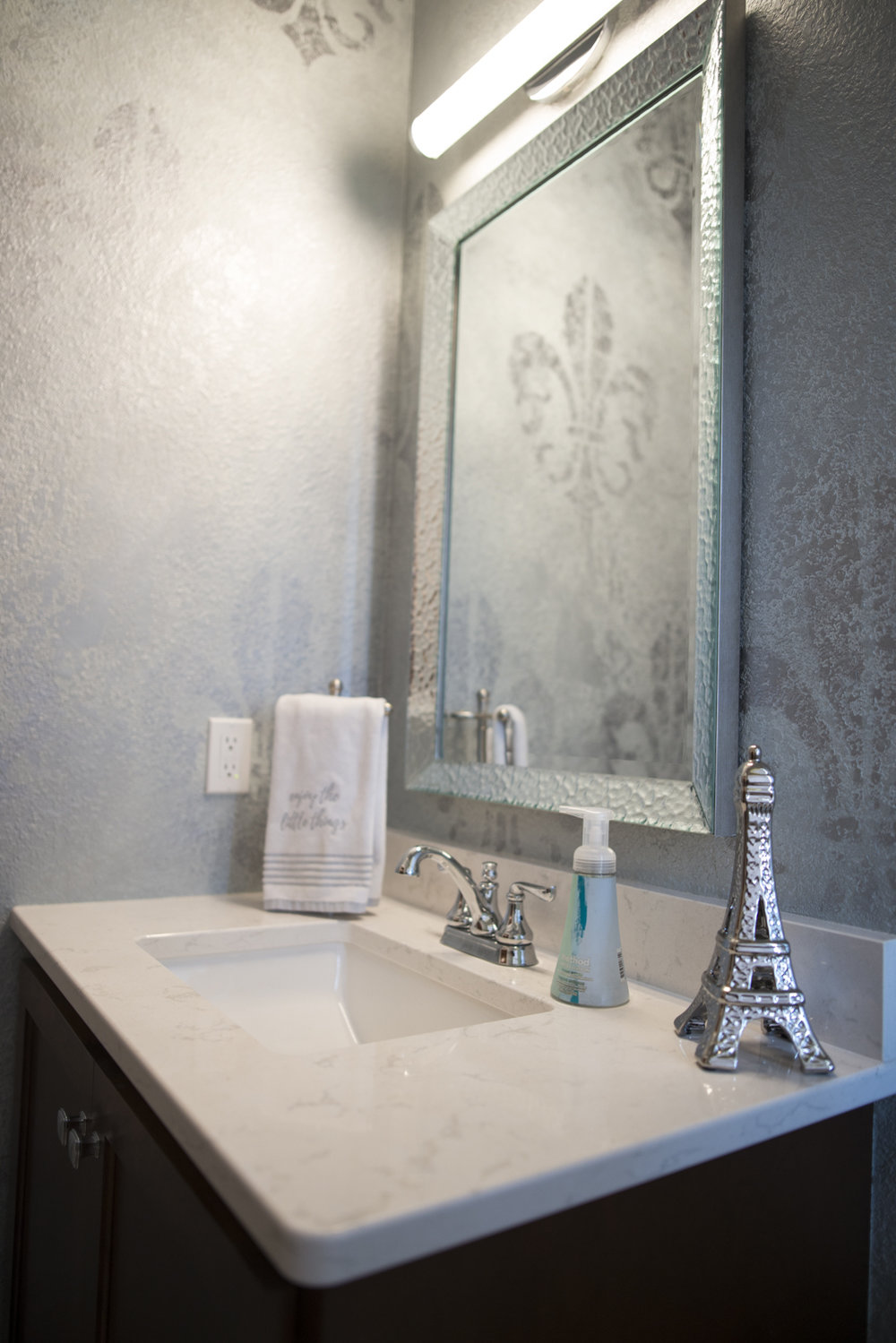 The half-bath walls were supposed to be smooth so they could be wallpapered, but due to a miscommunication with the builder it ended up with textured walls.  No problem, Maranda hired local paint artist, Caren Brumleve, to paint this effect on the wall.