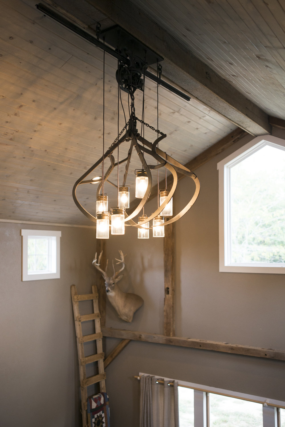 """""""There are many items I treasure, but my favorite is the light in my great room. It is made from the old hay hook and trolley that used to be in an old barn at our farm."""" The ladder came from the same place and the buck on the wall was John's """"big one""""."""