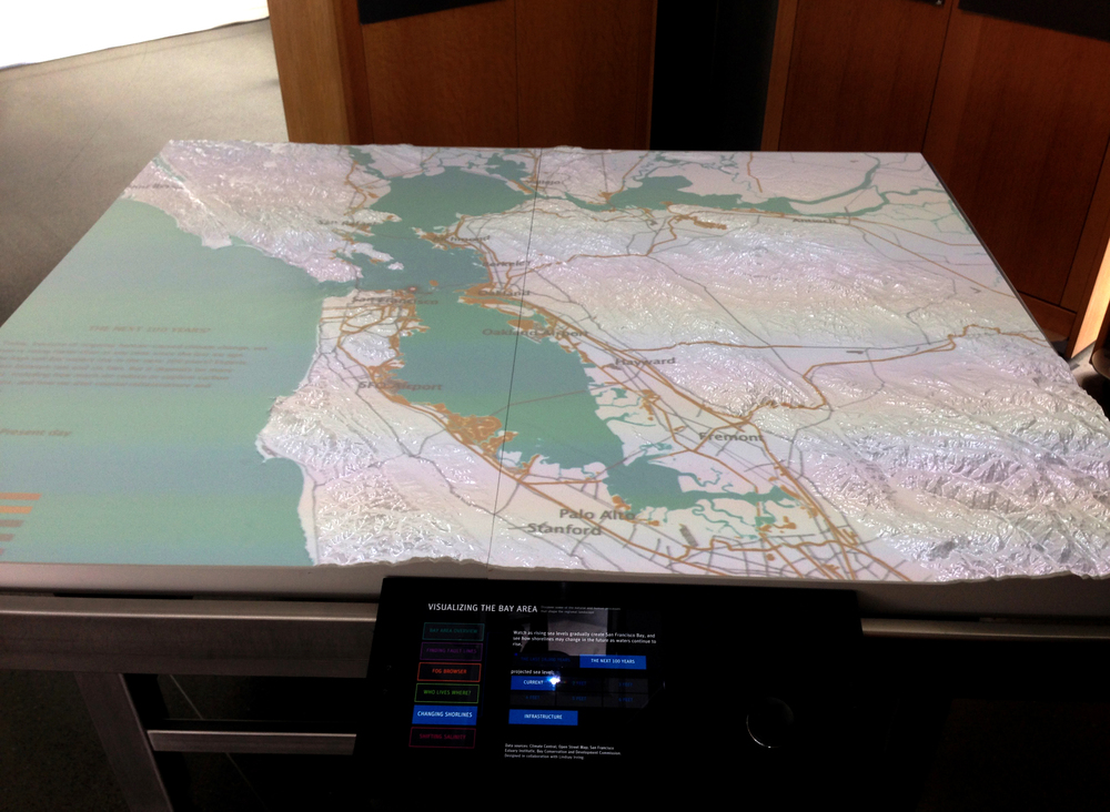 "Visitors can select the ""Past 18,000 years"" or ""the Next 100 years"" on a tablet and scroll through sea level elevations that are projected onto the 3D table. Data sources: USGS, NOAA, SFEI, Climate Central, UC Santa Barbara, MapZen's OSM MetroExtracts, Scripps Institute of Oceanography."