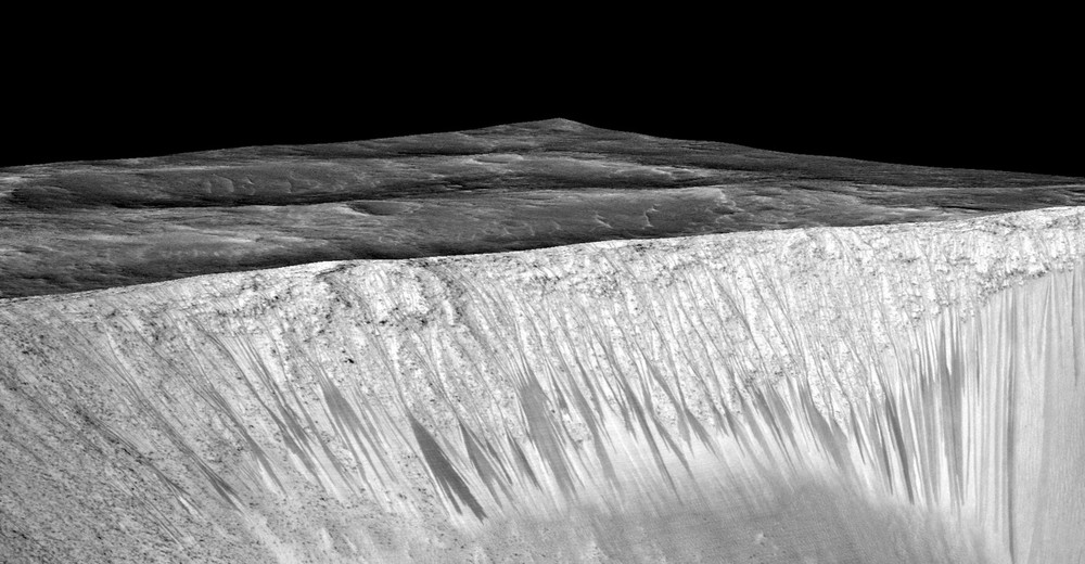 The dark narrow streaks are called recurring slope lineae and are formed by the seasonal flow on briny water on Mars. Photo: NASA/JPL/University of Arizona