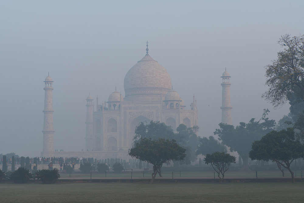 Orange glow from the rising sun on the white marble of the Taj Mahal.