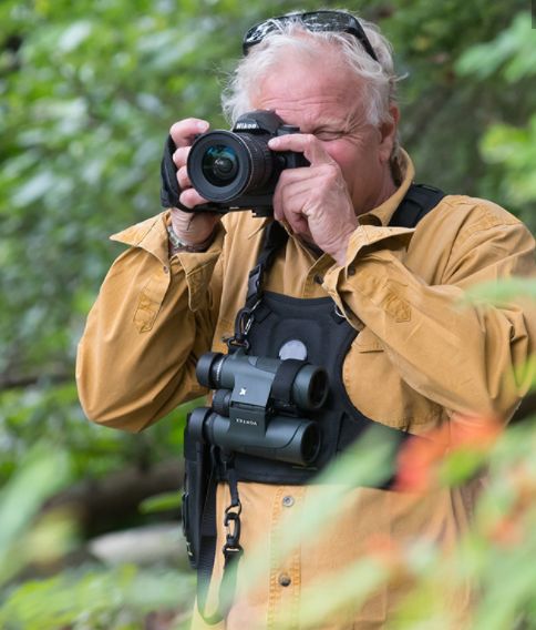 Image of a guy using the Binocular and Camera Harness from the Cotton Carrier website.