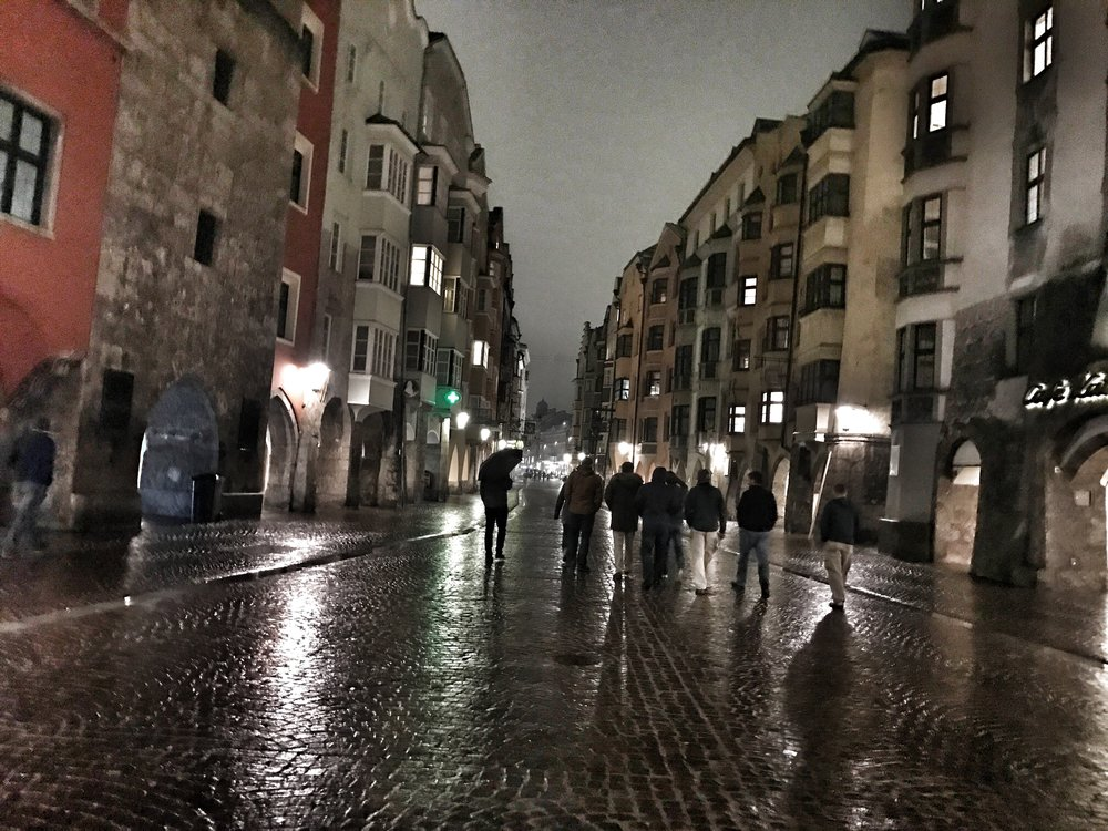 Birders wandering the streets of Innsbruck on a rainy night.