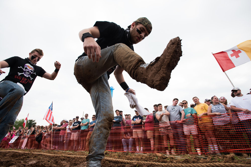 Sam Deering of Sigma Epsilon kicks footholds in the mud before squaring up against the Lambda Chi fraternity. Sigma Epsilon went on to win the tournament.