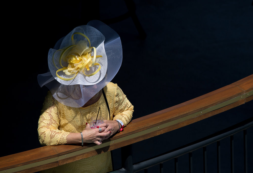 A woman watches the race from one of the upper balconies while drinking a Lily, one of the more popular drinks at The Derby.