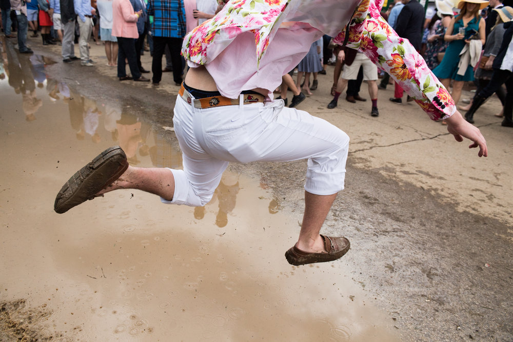 A man hops a puddle in the infield of Churchill Downs. The infield, known for its party atmosphere, was particularly muddy following the previous day's rainfall.