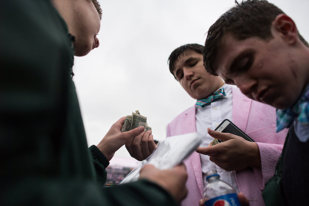 Money exchanges hands in the infield during the 2017 running of the Kentucky Oaks.