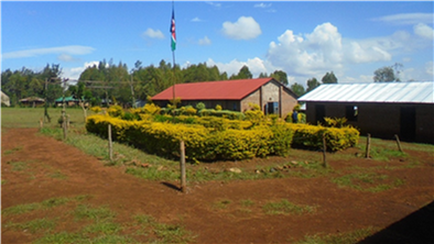 Our schoolyard including the red-roofed church, one of the metal-roofed classrooms, and the Kenyan flag in the middle