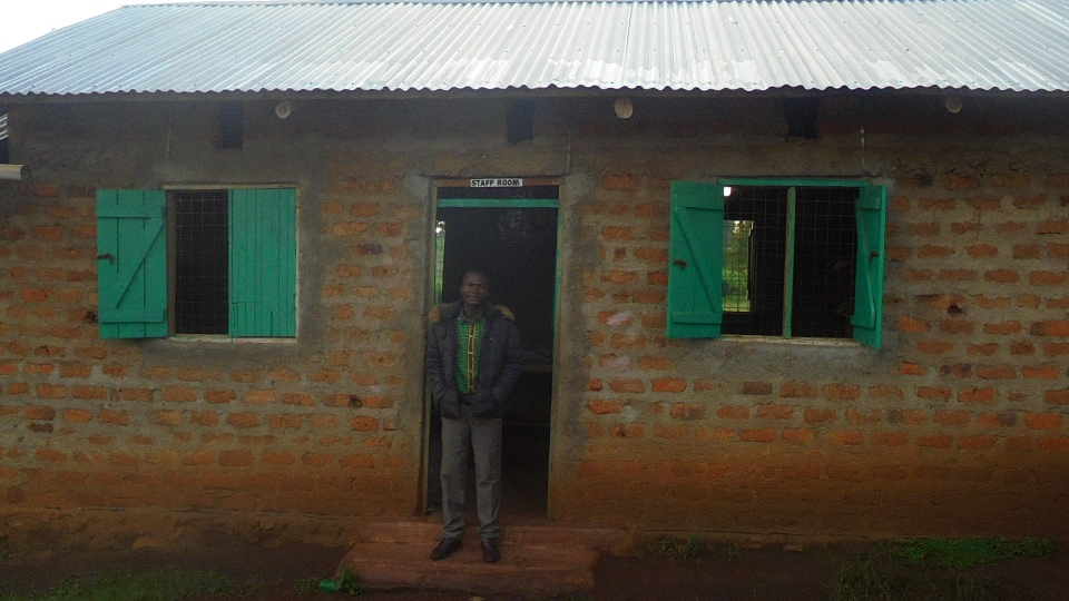 Moses, our science teacher, standing in front of the staffroom, where the administrative staff work and the teachers keep their supplies