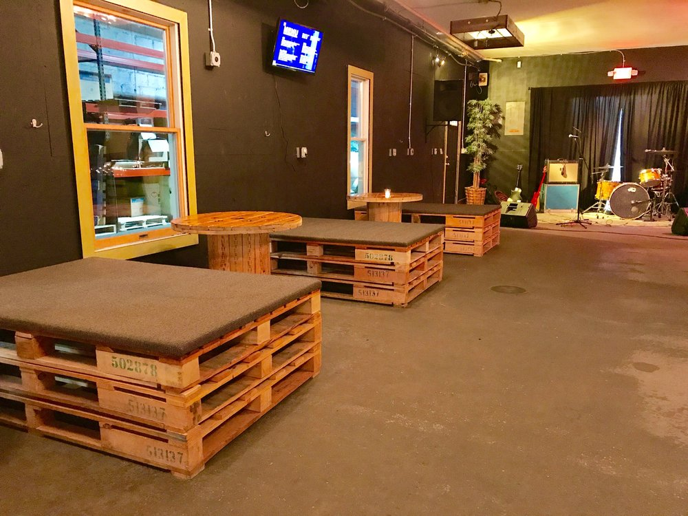 Reclaimed wood settees and tables create comfortable spaces for sipping beer and listening to live music.