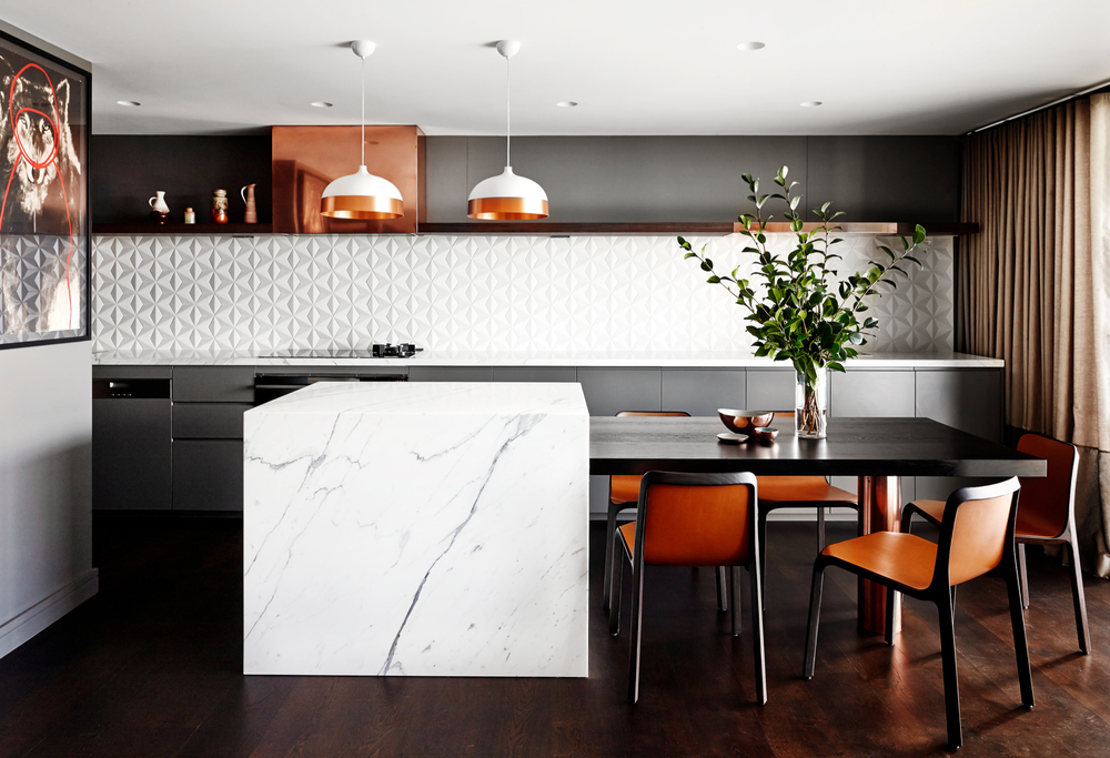 We love the textured tile splash back in our Moore Park Gardens project. The flexible island bench-come-dining table extension creates the ideal entertainer's kitchen in an inner city pad. The timber floorboards throughout the kitchen and living spaces create a visual connection and feeling of space.