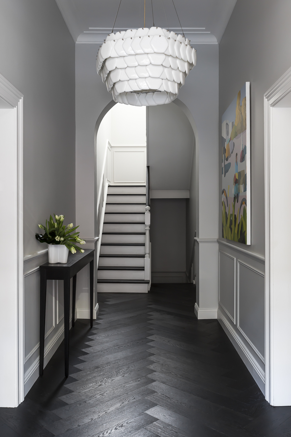 An elegant foyer proudly reveals strong features such as the new herringbone timber flooring, wall paneling and sculptural pendant light.