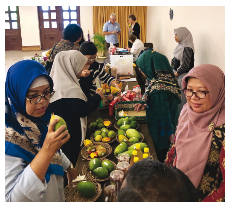 Workshop attendees sampling different mango varieties and products.