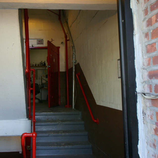 Then walk up half a flight of stairs and open the large, red metal door to find the distillery.