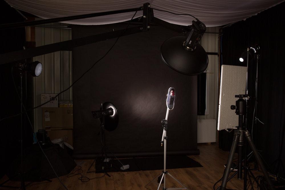 Een kijkje achter de schermen. De zwarte gordijnen aan de zijkanten voorkomen dat het flitslicht terugkaatsen en voor minder contrast zorgen. Ik heb 4 studiolampen gebruikt, drie voor de schoen en één voor de achtergrond. Ik heb vandaag twee verschillende beelden gemaakt.