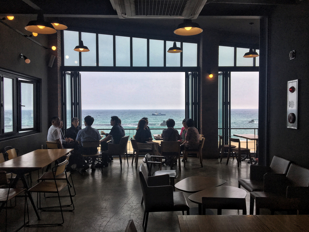Interior of AM Bread & Coffee with a view of Anmok Beach.
