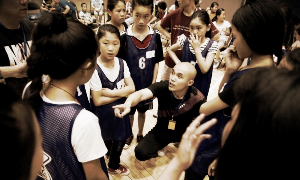 A girls' basketball team huddles at the 2014 TALENT graduation, where all schools played against each other.