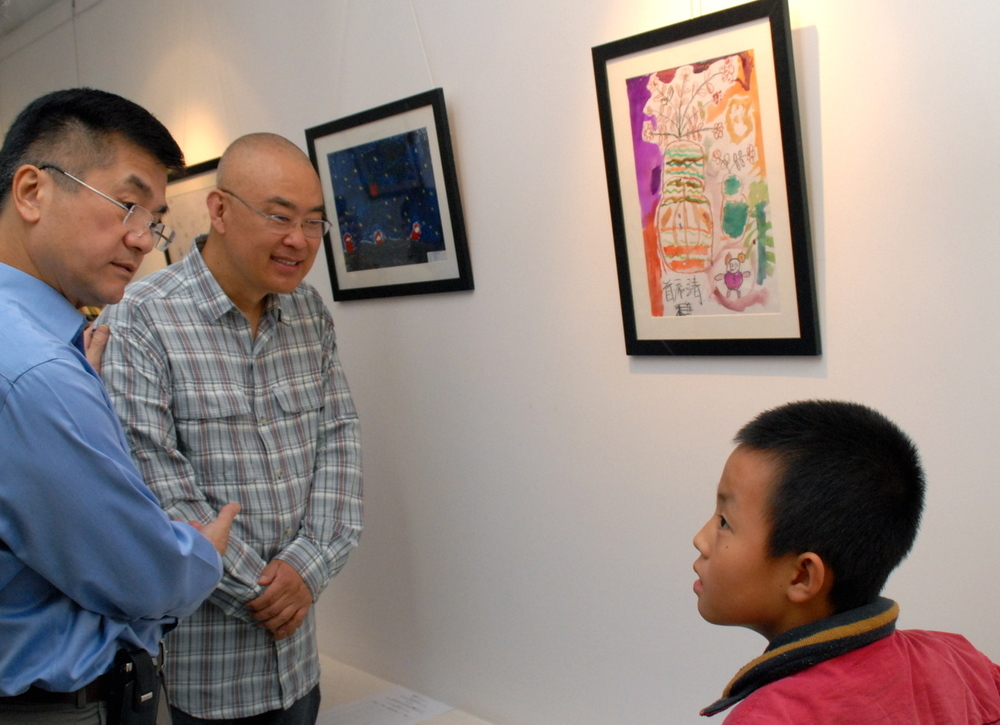 US Ambassador Gary Locke (left) and children's author Zheng Yuanjie chat to 10-year-old Shou Tianjing, a pupil at a Beijing migrant school, about his artwork during an ABC fundraising event. (Courtesy of US Embassy, Beijing)