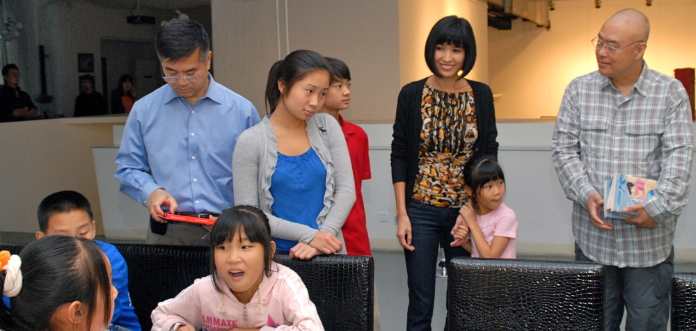 Ambassador Locke and his family and author Zheng Yuanjie (right) take part in an art activity with migrant children (sitting) in Beijing, September 2011. (Courtesy of US Embassy, Beijing)