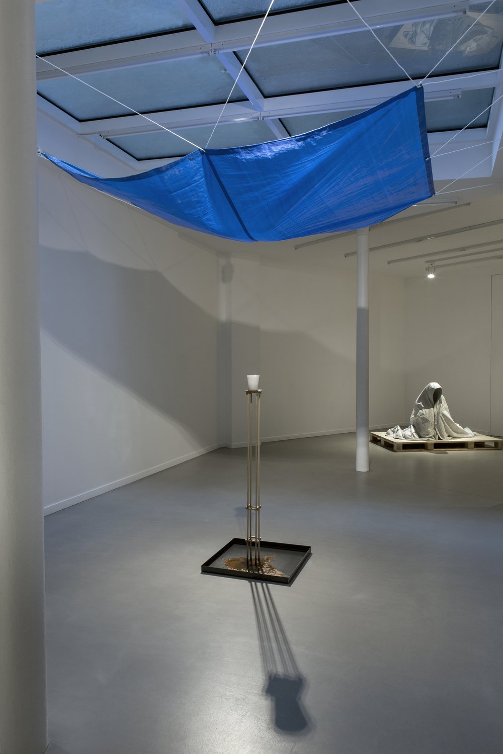 Deluge in a Cup   2015  Bianca Carrara, stainless steel tray, tarp, water, rope, Tasmanian oak stand  Dimensions variable (foreground)