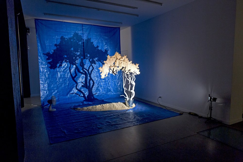 The Best of All Possible Worlds  2015, Bianca Carrara, tarp, tin bucket, sand, light, fan, dimensions variable