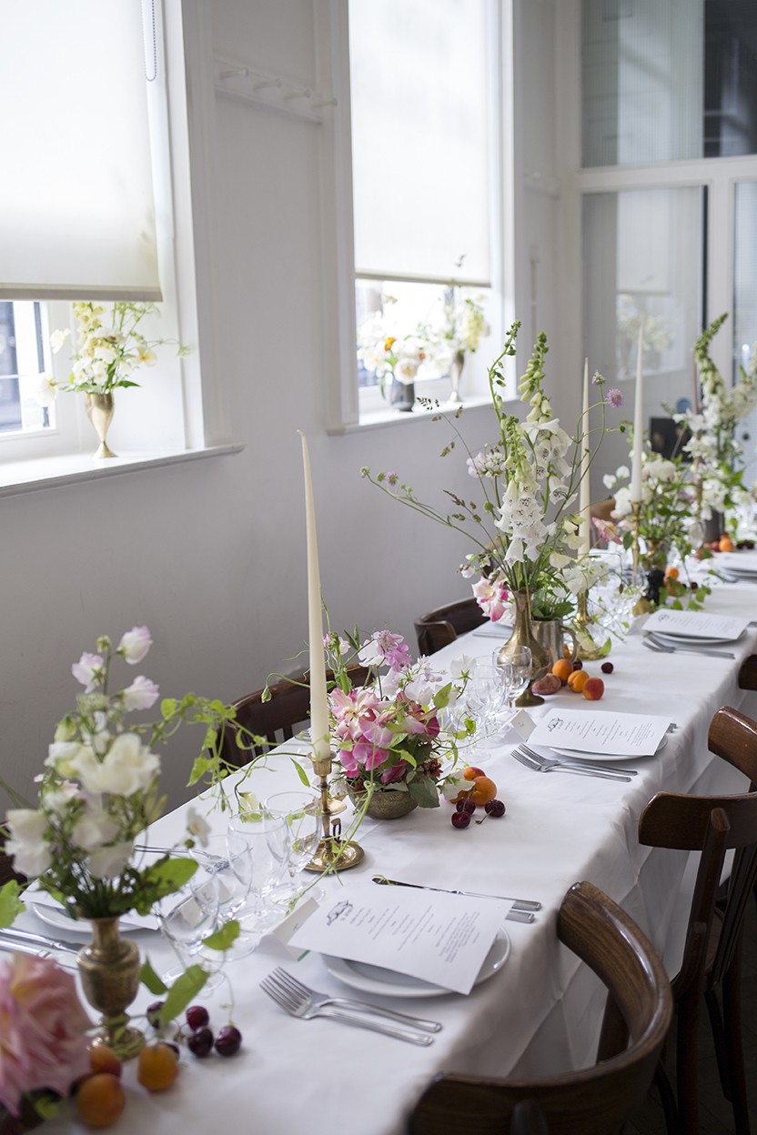 Table arrangements of June foxgloves, sweet peas and poppies, in vintage vessels with tapered candles and seasonal fruit