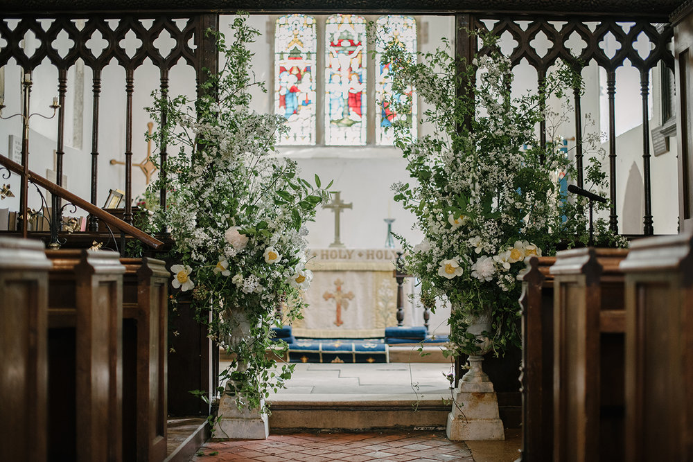 We decorated the church with a pair of antique urns, cascading with fresh green branches, white blossom and lemon centred  Claire de Lune  peonies